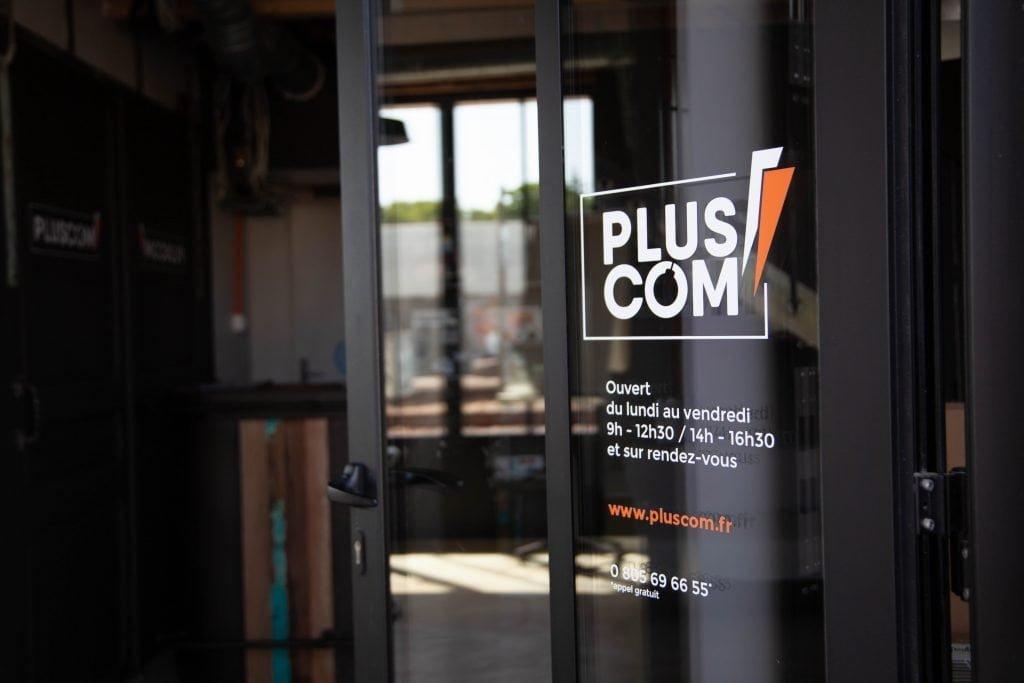 Panneau de la porte de l'agence de communication PLUSCOM à La Rochelle